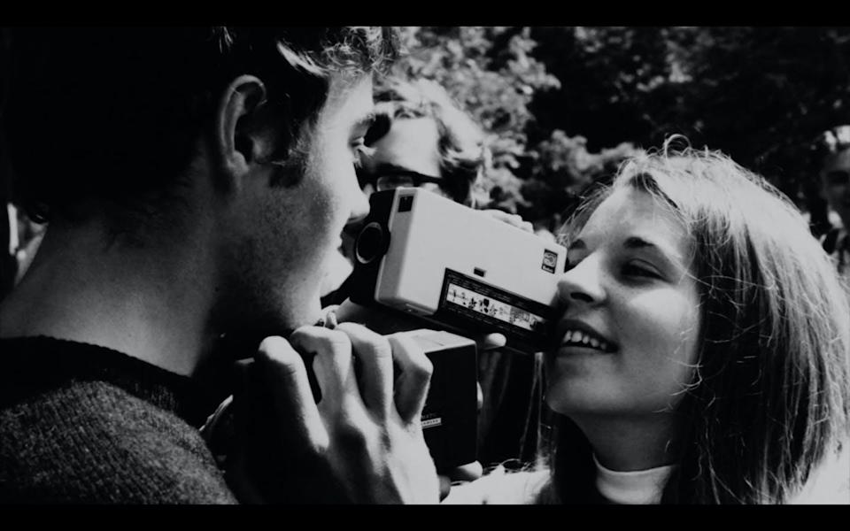 A black and white photo of a young girl using a hand-held camera to photograph a young man.