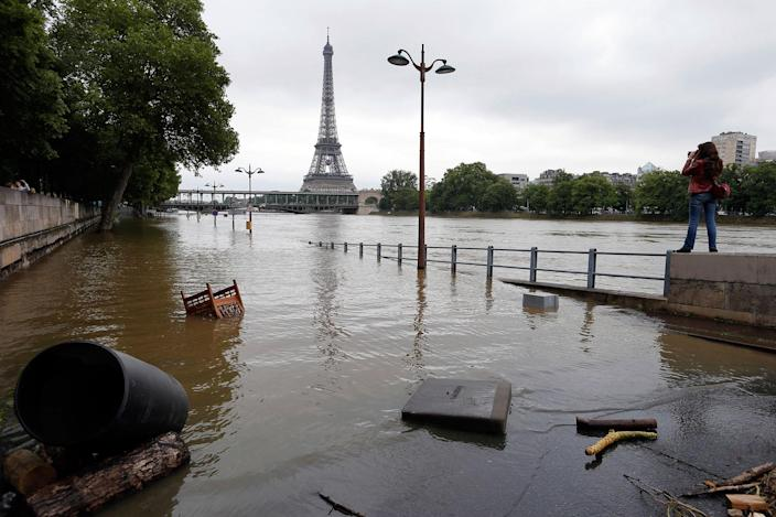 <p>A woman, at right, takes photos of the flooded banks of the Seine river in Paris, June 4, 2016. An international team of scientists has found that man-made climate change nearly doubled the likelihood of last month's devastating French flooding. In a quick but not peer reviewed analysis, the World Weather Attribution team of climate scientists used past rainfall data and computer simulations to look for global warming's fingerprints in the heavy downpours in France and Germany. (AP Photo/Francois Mori) </p>