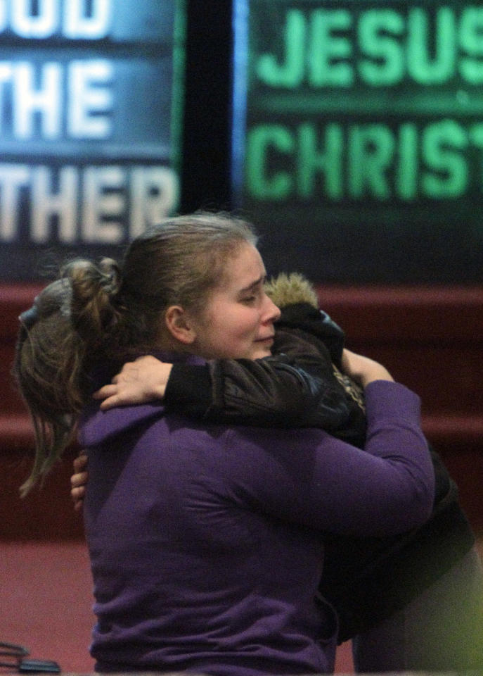 Alissa Sully, 17, hugs a friend before a prayer service for victims of a school shooting at Chardon Assembly of God in Chardon, Ohio Monday, Feb. 27, 2012. A gunman opened fire inside the high school's cafeteria at the start of the school day Monday, killing one student and wounding four others. (AP Photo/Mark Duncan)