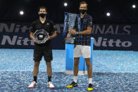 Daniil Medvedev of Russia, right, holds up the winners trophy after defeating Dominic Thiem of Austria, left, in the final of the ATP World Finals tennis match at the ATP World Finals tennis tournament at the O2 arena in London, Sunday, Nov. 22, 2020. (AP Photo/Frank Augstein)
