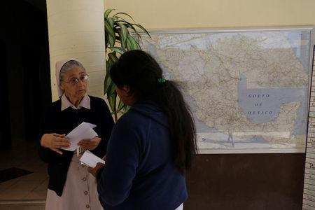 Sister Edith explains Mexican deportee Silvia how to take a bus back to his town in Oaxaca at Our Lady of Guadalupe migrant shelter in Reynosa, Mexico March 14, 2017. Picture taken March 14, 2017. REUTERS/Daniel Becerril