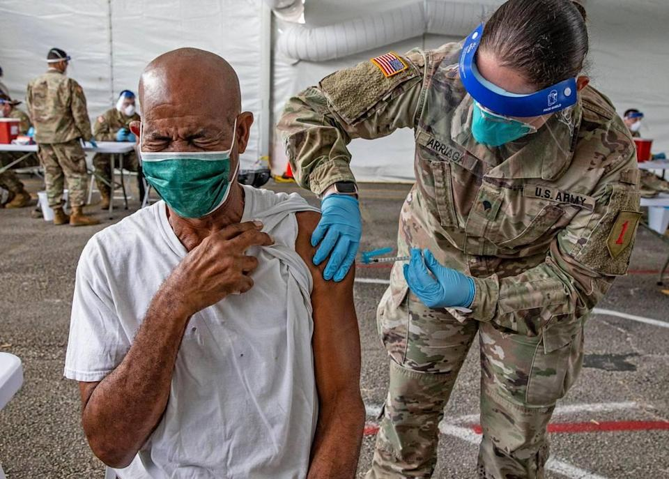 Ralph Morris, 67, is injected with a COVID-19 vaccine by a U.S. Army medic during opening day of the FEMA vaccination site on Miami Dade College's North Campus on Wednesday, March 3, 2021.