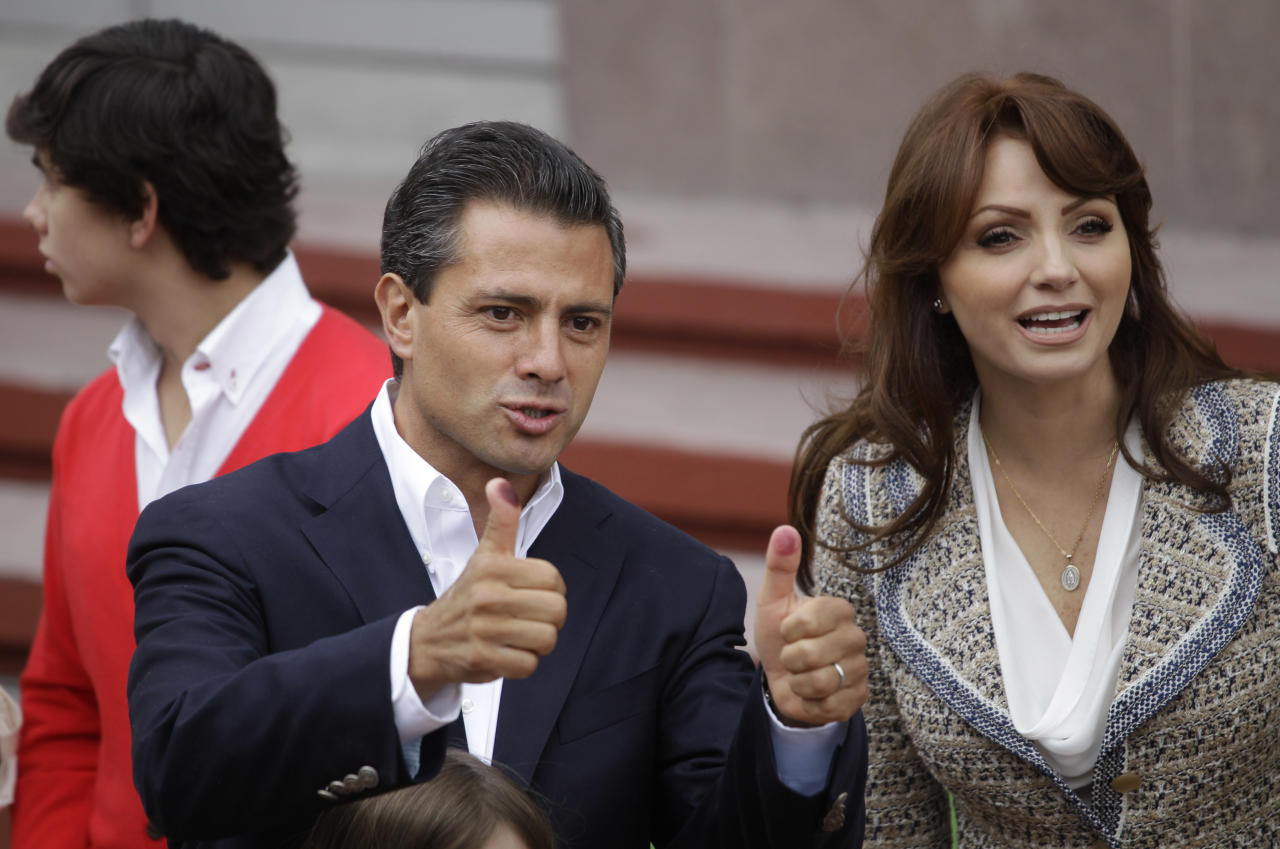 Enrique Pena Nieto, presidential candidate for the Revolutionary Institutional Party (PRI), accompanied by his wife Angelica Rivera, flashes his election ink-stained thumbs after he cast his vote in the general election in Atlacomulco, Mexico, Sunday, July 1, 2012. According to polls, the PRI, holds a sizeable lead in these elections, after being kicked out of the top office by voters 12 years ago. At right is Pena Nieto's wife, Angelica Rivera. (AP Photo/Dario Lopez-Mills)