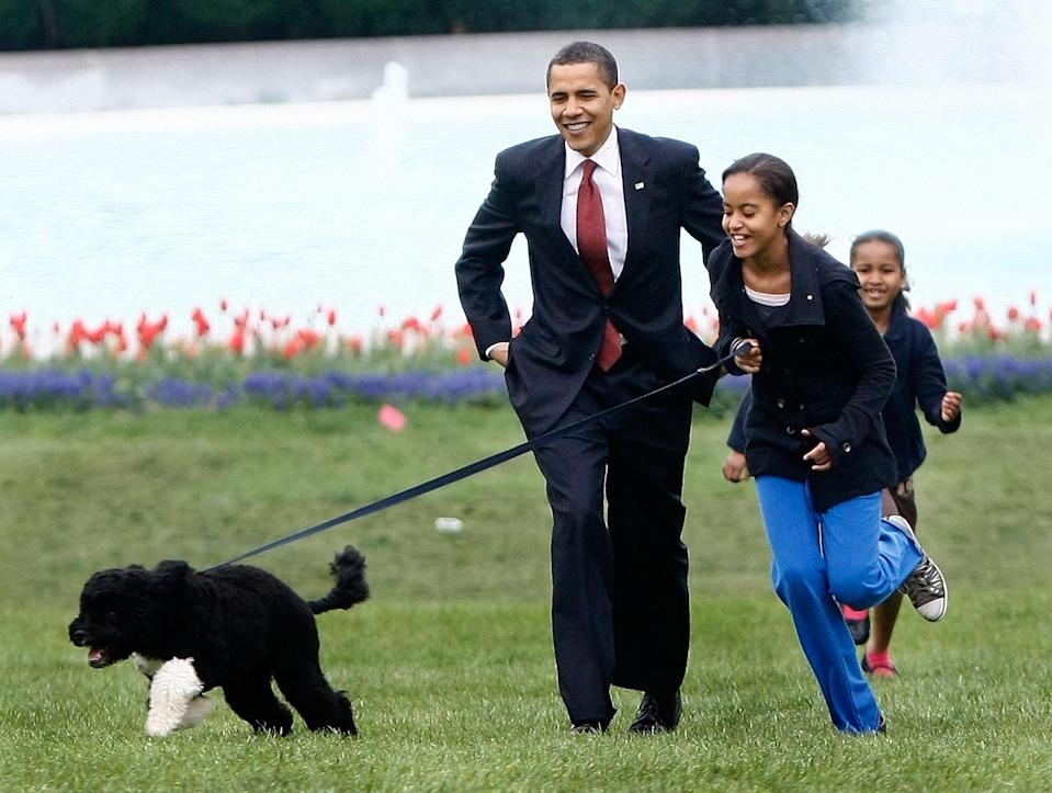 <p>President Barack Obama and his daughters Malia and Sasha spend time playing with their Portuguese water dog Bo ahead of the pup's official introduction to the White House press corps in April 2009.</p>