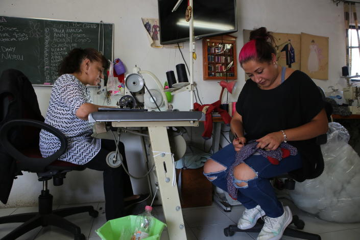 Ziomara Guzman de la Parra, right, and Maria Luna Ramirez, work at making teddy bears made with pieces of clothing that were worn by a COVID-19 victim, in the workshop of seamstress Irma de la Parra, in Mexico City, Saturday, April 24, 2021. De la Parra used to make teachers' gowns, but school closings during the pandemic left her without a job. She took it upon herself to make teddy bears out of clothing from those who died of COVID-19 to give those who are still alive a chance to grieve and be closer to those they were unable to bid farewell to. (AP Photo/Ginnette Riquelme)