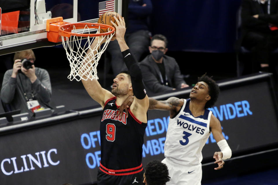 Chicago Bulls center Nikola Vucevic (9) is fouled by Minnesota Timberwolves forward Jaden McDaniels (3) in the first quarter of an NBA basketball game, Sunday, April 11, 2021, in Minneapolis. (AP Photo/Andy Clayton-King)