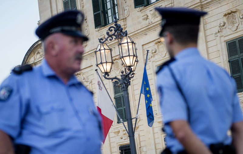 Police officers patrol during a vigil to commemorate journalist Daphne Caruana Galizia,in Castile square, outside the office of the prime minister in Malta, Tuesday, Oct. 17, 2017. Daphne Caruana Galizia, the Maltese investigative journalist who exposed the island nation's links to offshore tax havens through the leaked Panama Papers, was killed Monday when a bomb exploded in her car. (AP Photo/ Rene Rossignaud)