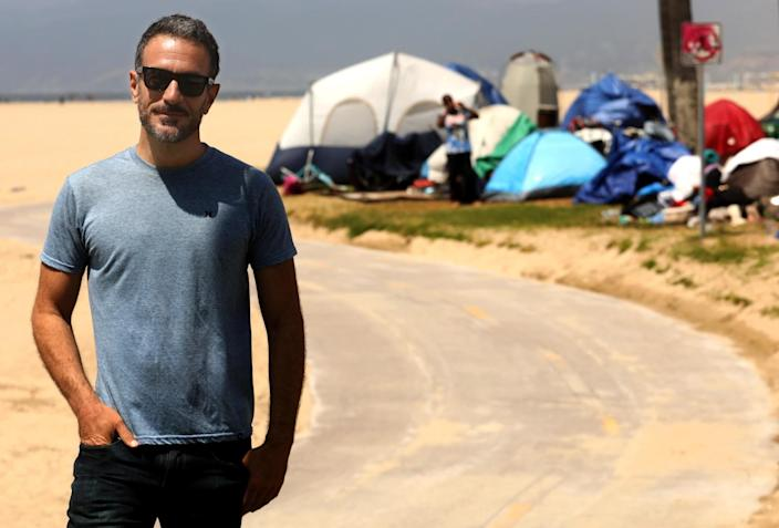 Brian Averill stands in front of a homeless camp
