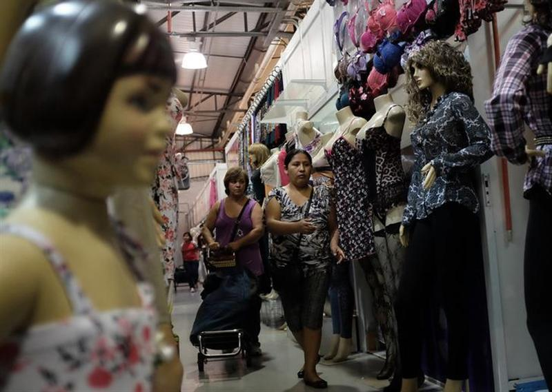 A Bolivian immigrant (R) sells clothes to a Brazilian woman at a shop, in the Bras neighbourhood of Sao Paulo early morning August 9, 2013.