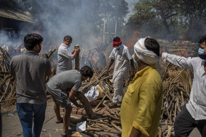 Members of a family of COVID-19 victim prepare funeral pyre for deceased member as multiple funeral pyres of those who died of COVID-19 are seen at a crematorium in New Delhi, India, Saturday, April 24, 2021. Delhi has been cremating so many bodies of coronavirus victims that authorities are getting requests to start cutting down trees in city parks, as a second record surge has brought India's tattered healthcare system to its knees. (AP Photo/Altaf Qadri)