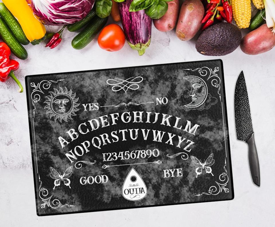 """Soyou can summon a spirit into your kitchen each time you cut up meat, fish or produce. Just kidding ... it WILL make your kitchen look super cool, though. Say10Craftsis a small business that sells a variety of gothic and occult clothing, home goods, face masks and more spooky goodness!<br /><br /><strong><a href=""""https://go.skimresources.com?id=38395X987171&xs=1&xcust=HPKitchenProductsDidntKnowExisted60a3fc0fe4b063dcceaf8560-&url=https%3A%2F%2Fwww.etsy.com%2Flisting%2F870146065%2Fouija-board-gothic-home-decor-ouija"""" target=""""_blank"""" rel=""""noopener noreferrer"""">Get it from Say10Crafts on Etsy for $39.60+ (available in two sizes).</a></strong>"""