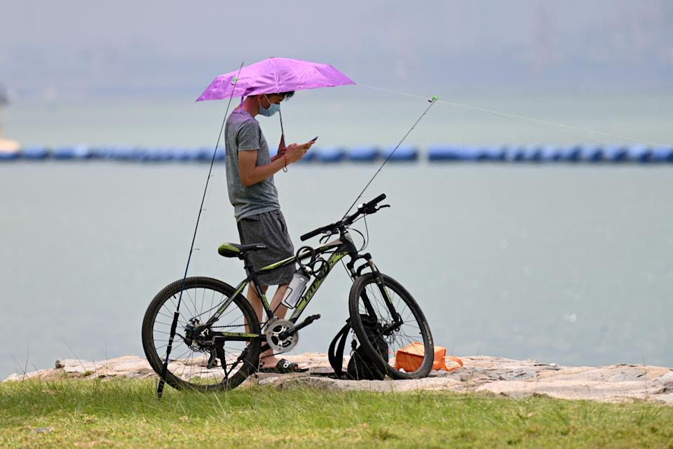 A man looks on his mobile phone while fishing along a beach in Singapore on April 13, 2021. (Photo by Roslan RAHMAN / AFP) (Photo by ROSLAN RAHMAN/AFP via Getty Images)