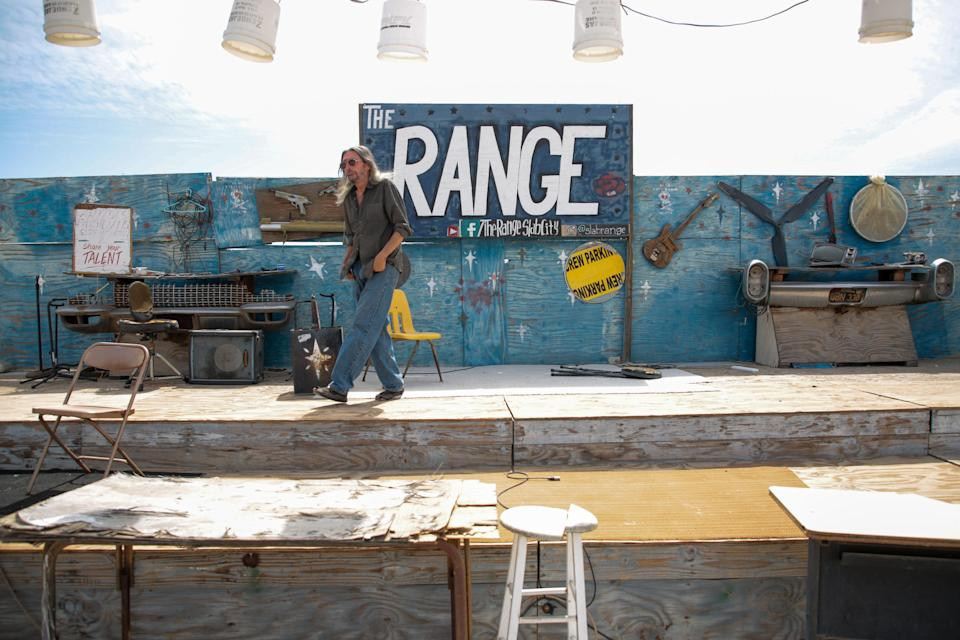 Carlos Gonzales walks on the stage of The Range in Slab City, Calif., on Monday, April 5, 2021. Gonzales received both doses of his COVID-19 vaccine and looks forward to playing guitar at The Range in front of an audience after the venue's hiatus due to the pandemic.