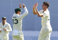 Australia's Pat Cummins, right, is congratulated by teammate Matthew Wade after taking the wicket of India's Shardul Thakur during play on day three of the fourth cricket test between India and Australia at the Gabba, Brisbane, Australia, Sunday, Jan. 17, 2021. (AP Photo/Tertius Pickard)