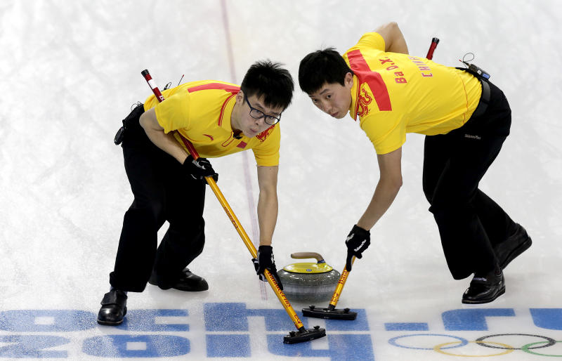 China's Zang Jialiang, left, and Ba Dexin, right, sweep the ice during the men's curling competition against Germany at the 2014 Winter Olympics, Wednesday, Feb. 12, 2014, in Sochi, Russia. (AP Photo/Wong Maye-E)