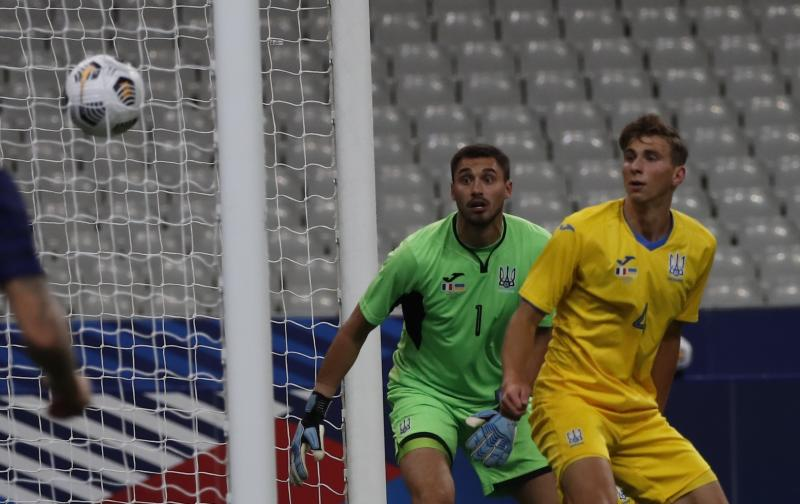 The ball goes into the net ahead as two Ukraine players watch.