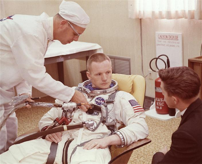 """FILE - In this March 9, 1966 file photo, astronaut Neil Armstrong is seated during a suiting up exercise Cape Kennedy, Fla., in preparation for the Gemini 8 flight. The family of Neil Armstrong, the first man to walk on the moon, says he died Saturday, Aug. 25, 2012, at age 82. A statement from the family says he died following complications resulting from cardiovascular procedures. It doesn't say where he died. Armstrong commanded the Apollo 11 spacecraft that landed on the moon July 20, 1969. He radioed back to Earth the historic news of """"one giant leap for mankind."""" Armstrong and fellow astronaut Edwin """"Buzz"""" Aldrin spent nearly three hours walking on the moon, collecting samples, conducting experiments and taking photographs. In all, 12 Americans walked on the moon from 1969 to 1972. (AP Photo/File)"""
