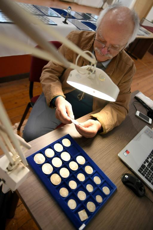 Archaeologist and coin expert Ferenc Redo says almost half of the coins are from the Roman era (AFP Photo/ATTILA KISBENEDEK)