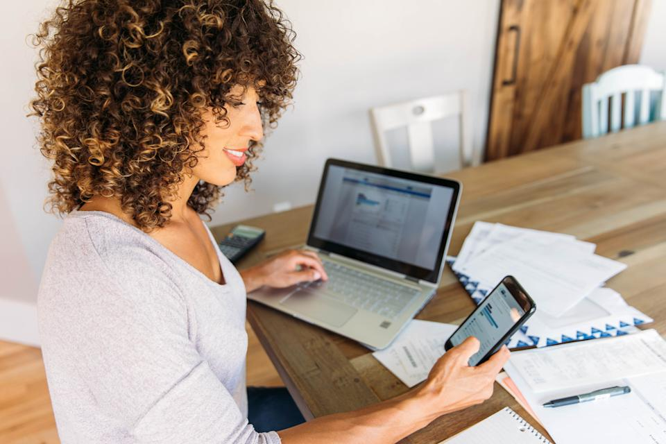 A woman sits at her dining room table with laptop and financial reports doing her monthly budget. She is smiling at the ease of use as she works on her smart phone banking app to do monthly finances, pay taxes and save money for the future.