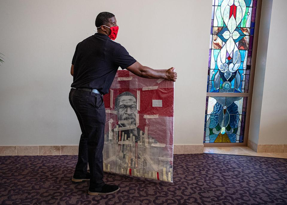 """A man moves a painting of George Floyd at the funeral in Houston.<span class=""""copyright"""">Ruddy Roye for TIME</span>"""