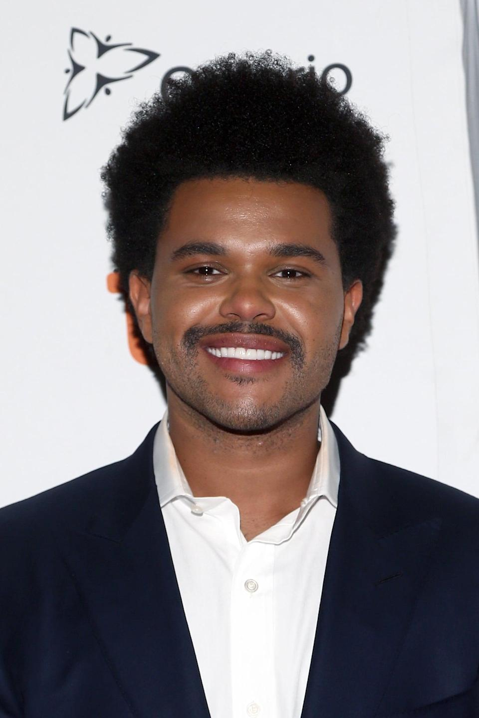 """<p>In 2019, he stepped out at a film festival wearing a <a href=""""https://www.popsugar.com/beauty/the-weeknd-new-hair-toronto-international-film-festival-46599064"""" class=""""link rapid-noclick-resp"""" rel=""""nofollow noopener"""" target=""""_blank"""" data-ylk=""""slk:slightly longer, more rounded afro"""">slightly longer, more rounded afro</a> and a horseshoe mustache.</p>"""