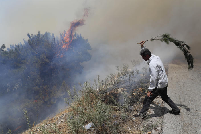 A man tries to extinguish a forest fire, at Qobayat village, in the northern Akkar province, Lebanon, Thursday, July 29, 2021. Lebanese firefighters are struggling for the second day to contain wildfires in the country's north that have spread across the border into Syria, civil defense officials in both countries said Thursday. (AP Photo/Hussein Malla)