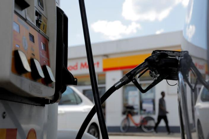 FILE PHOTO: A gas pump is seen in a car at a Shell gas station in Washington, D.C.