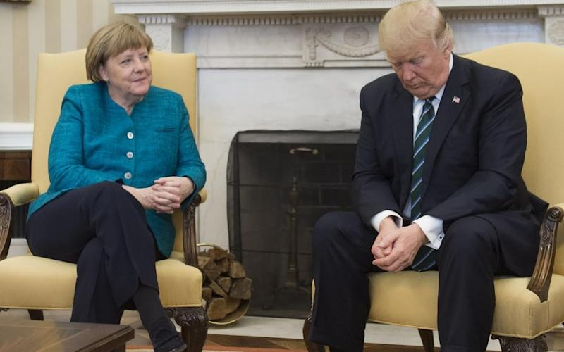 US President Donald Trump and German Chancellor Angela Merkel meet in the Oval Office - Credit: AFP
