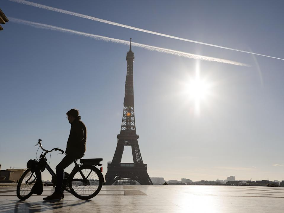 A man rides an electric bike in front of the Eiffel Tower during France's second coronavirus lockdown (AFP via Getty Images)