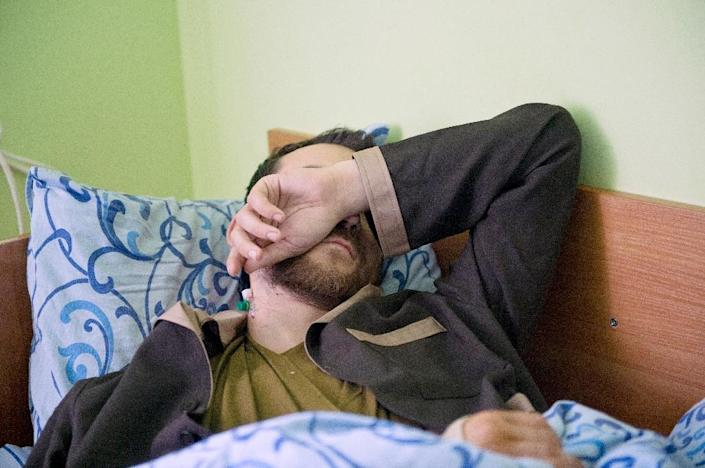 A man whom the Ukrainian security service allege to be a captured Russian soldier, covers his face as he recovers at Kiev military hospital on May 19, 2015 (AFP Photo/Genya Savilov)