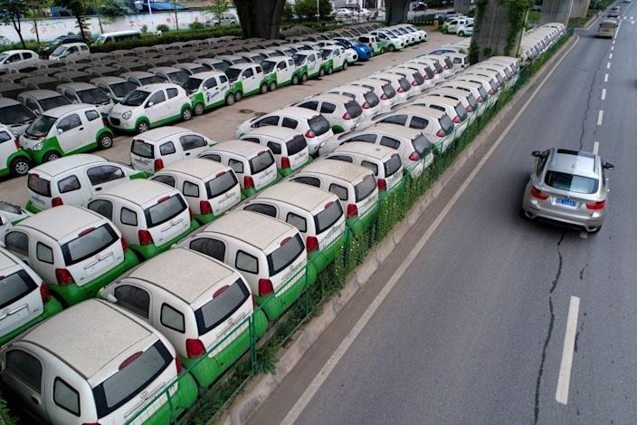 New electric vehicles parked in a parking lot under a viaduct in Wuhan, central China's Hubei province.