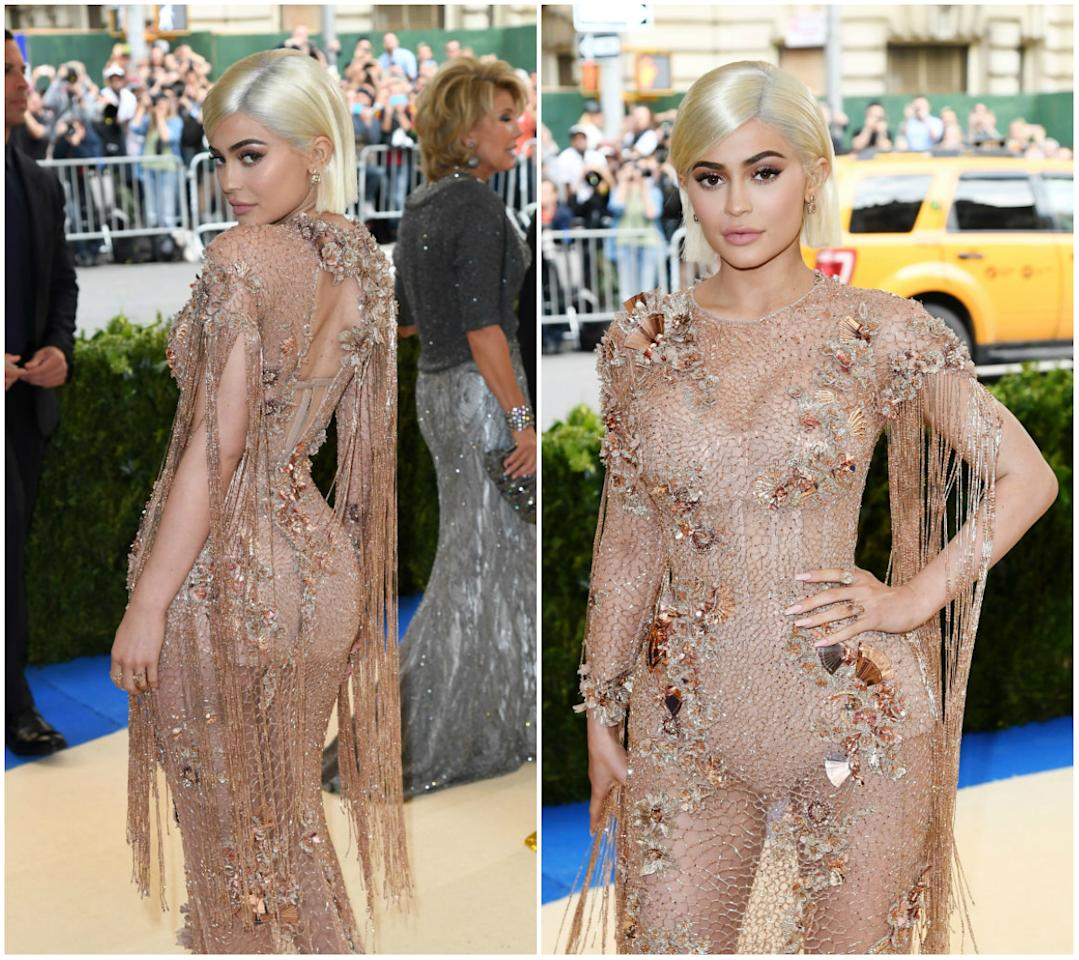 "<p>Kylie strutted the 2017 Met Gala red carpet in a gold see-through Atelier Versace dress that featured a fishnet lining and flowing ""waterfall"" fringes. The gown was completely sheer but luckily Kylie donned a skin-toned bodysuit underneath. She complemented the look with bleached-blonde tresses, and somehow managed to pull of a classy look. Thoughts? <i> (Photos: Getty) </i> </p>"
