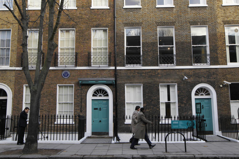 """People walk past Charles Dickens' home, left, part of the Charles Dickens Museum in London, Wednesday, Dec. 5, 2012. For years, the four-story brick row house where the author lived with his young family was a dusty and slightly neglected museum, a mecca for Dickens scholars but overlooked by most visitors to London. Now, after a 3 million pound ($4.8 million) makeover, it has been restored to bring the writer's world to life. Its director says it aims to look """"as if Dickens had just stepped out."""" (AP Photo/Sang Tan)"""