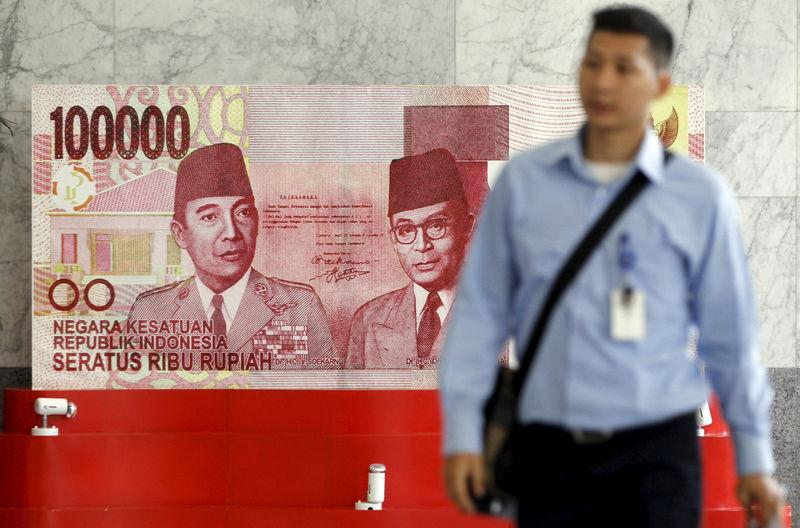 A man walks past a large display of a one hundred thousand rupiah banknote inside the Bank Indonesia complex in Jakarta, Indonesia