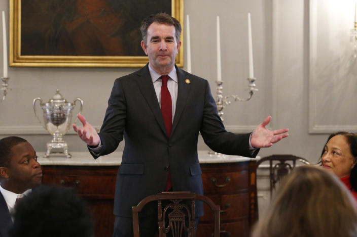 FILE - In this Friday, Feb. 22, 2019 file photo, Gov. Ralph Northam, center, greets members of the Richmond 34 and other African-American leaders for a breakfast at the Governors Mansion at the Capitol in Richmond, Va. The Richmond 34 were a group of African Americans who defied segregation laws in the 1960's. Two months after his political career was all but dead, life for Northam looks mostly back to normal. (AP Photo/Steve Helber)