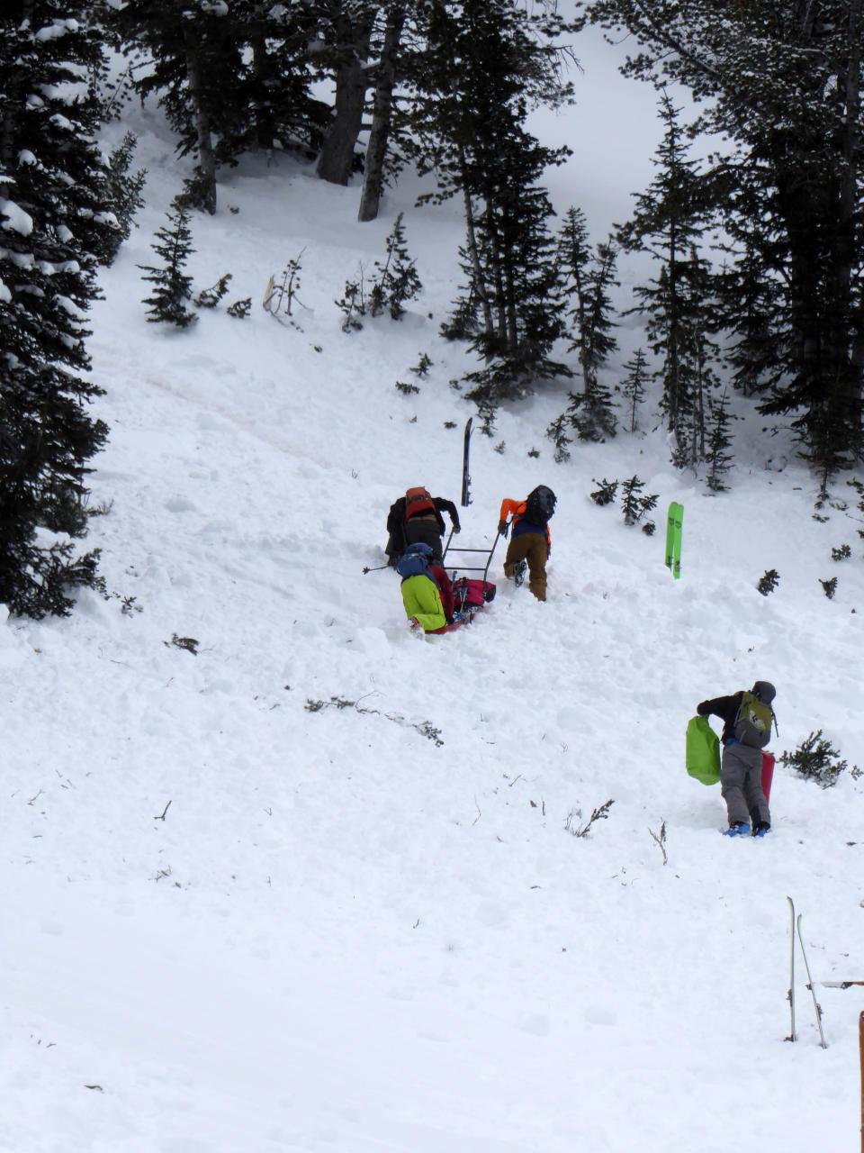 This aerial photo provided by Gallatin National Forest Avalanche Center shows a ground team approaching the area of an avalanche in the Gallatin National Forest, Mont., on Sunday, Feb. 14, 2021. A backcountry skier Craig Kitto, 45, of Bozeman, suffered fatal injuries when the Gallatin National Forest slope he and a companion were climbing cracked without warning, collapsed and swept him downhill into a tree. The other person wasn't hurt. (Gallatin National Forest Avalanche Center via AP)