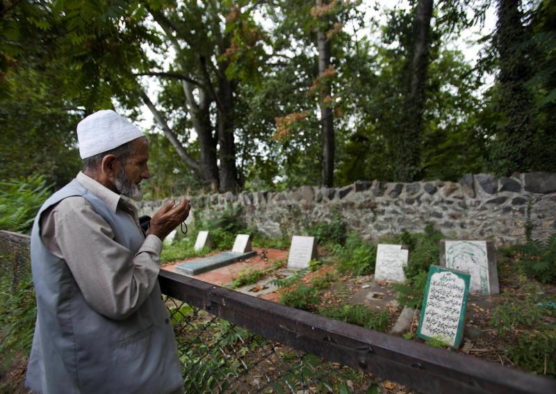 "FILE - In this Sept. 5, 2012 file photo, a Kashmiri Muslim prays near an unmarked grave, right foreground, that reads, ""unidentified fifteen year old boy shot and killed by Border Security Force soldiers on 5th September 2003,"" inside a martyrs graveyard in Srinagar, Indian controlled Kashmir. A prominent rights group in Indian-controlled Kashmir is advocating United Nations to establish a commission of inquiry to probe endemic use of torture by government forces who have faced decades long anti-India uprising in the disputed region. (AP Photo/ Dar Yasin, File)"