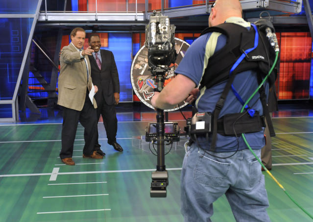 FILE - In this Oct. 26, 2008, file photo, Chris Berman, left, gestures during a live segment of Sunday NFL Countdown with colleague Tom Jackson at ESPN in Bristol, Conn. NFL PrimeTime with Berman and Jackson is coming back after a 14-year absence. ESPN+ is bringing back the popular highlights show beginning Sunday, Sept. 15, 2019. (AP Photo/Jessica Hill, File)