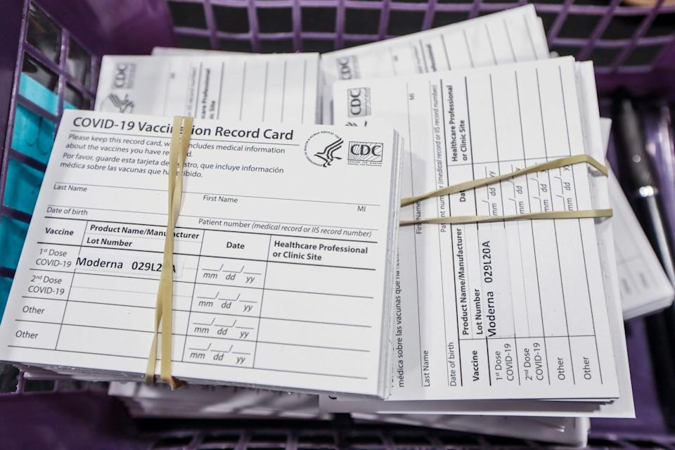 A stack of vaccine cards wait to be handed out to registered residents after they receive their Moderna COVID-19 vaccines from the Oakland County Health Division at Suburban Showplace in Novi, Mich. on Jan. 23, 2021.