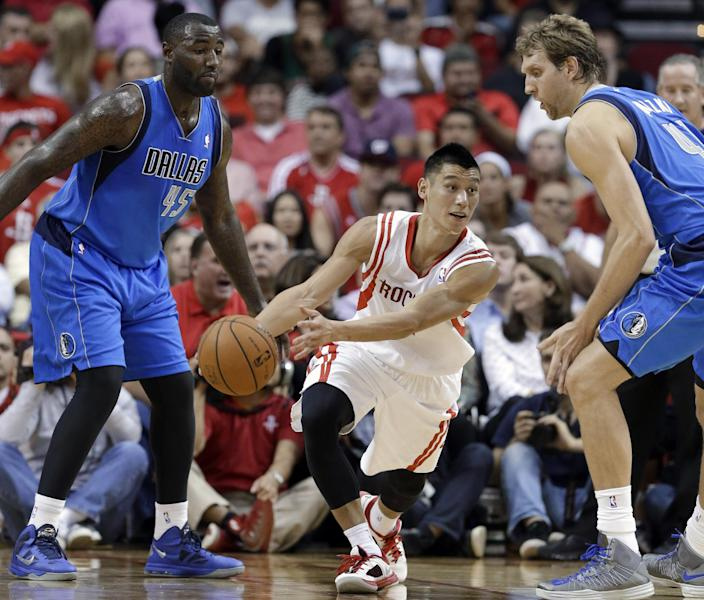 Houston Rockets' Jeremy Lin, center, passes the ball between Dallas Mavericks Vince Carter (25) and Dirk Nowitzki (41) in the first half of an NBA basketball game Friday, Nov. 1, 2013, in Houston. (AP Photo/Pat Sullivan)