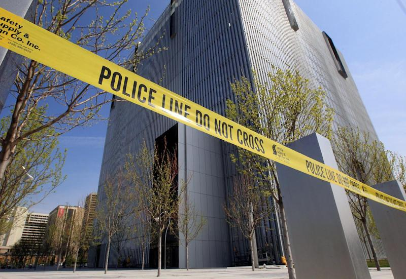 Police tape surrounds the Federal Courthouse Monday, April 21, 2014, in Salt Lake City. A U.S. marshal shot and critically wounded a defendant on Monday in a new federal courthouse after the man rushed the witness stand with a pen at his trial in Salt Lake City, authorities said. (AP Photo/Rick Bowmer)