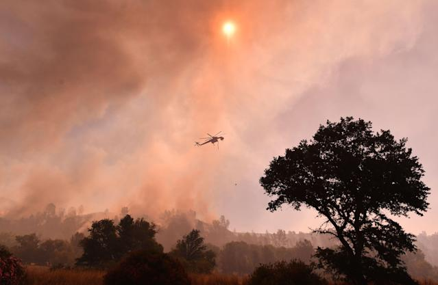 <p>A water dropping helicopter works the scene as the Pawnee fire jumps across highway 20 near Clearlake Oaks, Calif. on July 1, 2018. (Photo: Josh Edelson/AFP/Getty Images) </p>