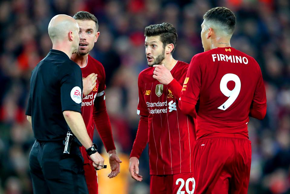 Liverpool's Jordan Henderson (second left), Adam Lallana and Roberto Firmino speak to Referee Anthony Taylor as he calls for VAR to check Sadio Mane's goal during the Premier League match at Anfield Stadium, Liverpool. (Photo by Nick Potts/PA Images via Getty Images)