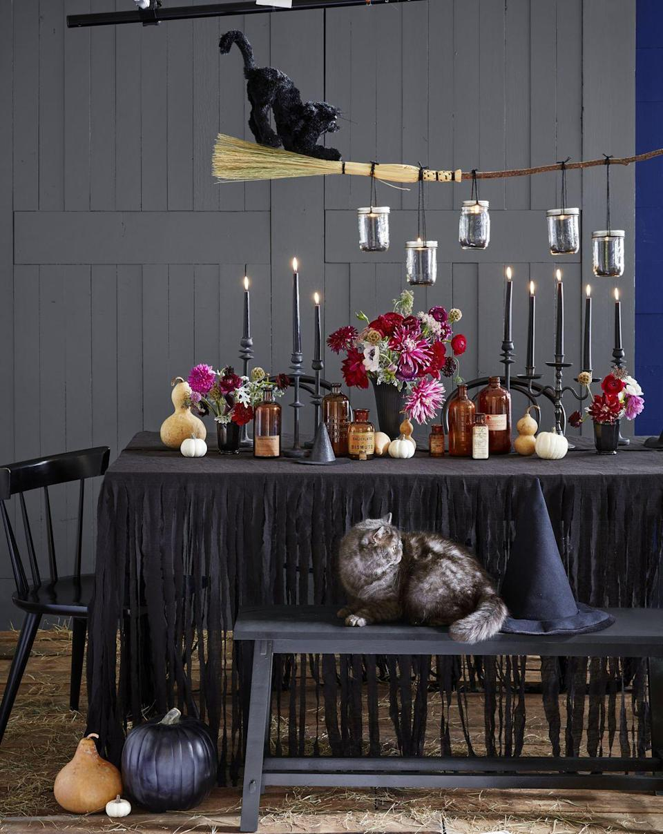 "<p>Surprise the guys and ghouls in your household this October 31 with a spook-tacular Halloween celebration. Keep things far from kitschy with a DIY broom chandelier, which you can hang <a href=""https://www.countryliving.com/diy-crafts/g1916/mason-jar-fall-crafts/"" rel=""nofollow noopener"" target=""_blank"" data-ylk=""slk:Mason jar"" class=""link rapid-noclick-resp"">Mason jar</a> candles from using black twine. Shred a black linen tablecloth for extra eerie flair, then add black furniture, candlesticks, and votives. </p><p><a class=""link rapid-noclick-resp"" href=""https://www.amazon.com/LinenTablecloth-126-Inch-Rectangular-Polyester-Tablecloth/dp/B008TL8DLU/?tag=syn-yahoo-20&ascsubtag=%5Bartid%7C10050.g.2633%5Bsrc%7Cyahoo-us"" rel=""nofollow noopener"" target=""_blank"" data-ylk=""slk:SHOP BLACK TABLECLOTHS"">SHOP BLACK TABLECLOTHS</a></p>"