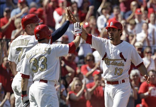 St. Louis Cardinals' Matt Carpenter (13) celebrates with teammates Daniel Descalso (33) and Matt Holliday (7) after scoring on a two-RBI single by Yadier Molina in the fourth inning of a baseball game against the Chicago Cubs, Saturday, April 14, 2012, in St. Louis. Holiday also scored on the play.(AP Photo/Tom Gannam)