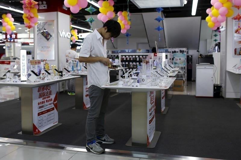 A customer look at a mobile phone on display at an electronics market in Shanghai