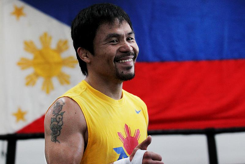 Filipino prizefighter Manny Pacquiao is framed by a flag of the Philippines as he opens training camp at the Wild Card Boxing Gym on March 9, 2015 in Los Angeles, California. (Photo: Luis Sinco/Los Angeles Times via Getty Images)