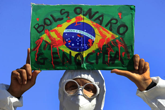 """A demonstrator holds an image of the Brazilian flag covered in fake blood and the Portuguese phrase """"Bolsonaro Genocide"""" during an anti-government protest by unions against President Jair Bolsonaro's policies to fight the COVID-19 pandemic in Brasilia, Brazil, Wednesday, May 26, 2021. (AP Photo/Eraldo Peres)"""