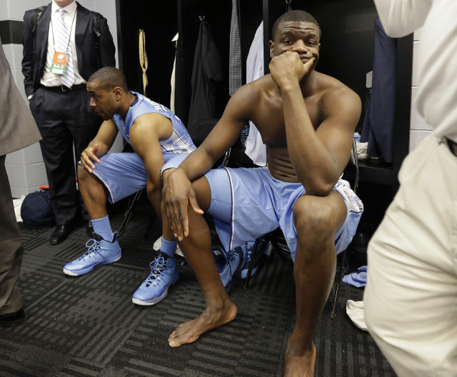 North Carolina's Denzel Robinson, left, and Joel James, right, sit in the locker room after the team's loss to Iowa State in a third-round game in the NCAA college basketball tournament Sunday, March 23, 2014, in San Antonio. Iowa State won 85-83. (AP Photo/Eric Gay)