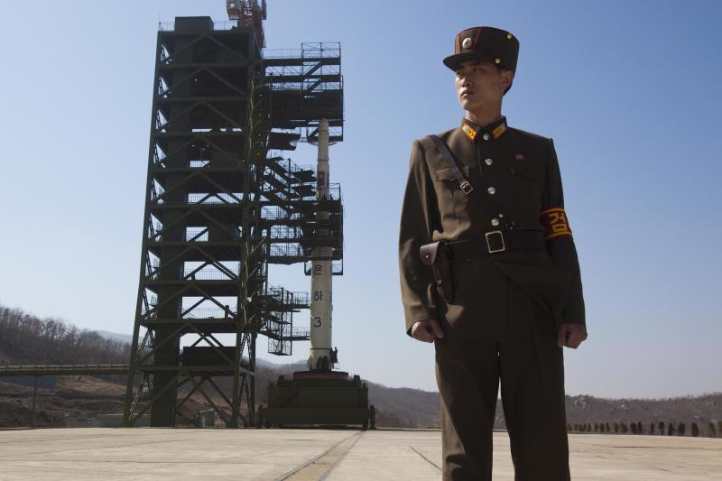 FILE - In this April 8, 2012 file photo, a North Korean soldier stands in front of the country's Unha-3 rocket, slated for liftoff between April 12-16, at Sohae Satellite Station in Tongchang-ri, North Korea. Rocket sections are apparently being trucked into North Korea's northwest launch site, but some analysts are asking whether it's just a calculated bluff meant to jangle the Obama administration and influence South Korean voters ahead of Dec. 19 presidential elections in three weeks. (AP Photo/David Guttenfelder, File)